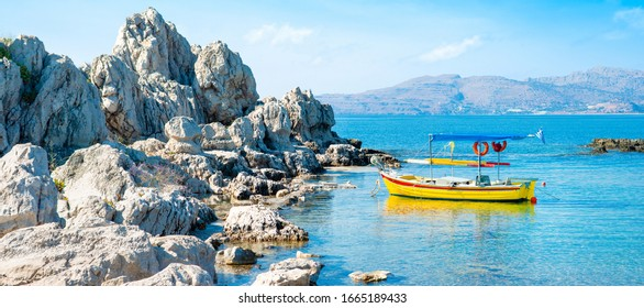 Beautiful landscape of the Mediterranean coast, with an old wooden fishing boat on the water, near a rocky beach
