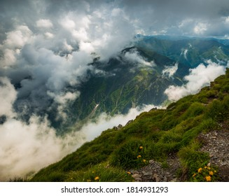 Beautiful landscape with misty mountains, steep ridges and green grass in Fagaras National Park, Transylvania, Romania.