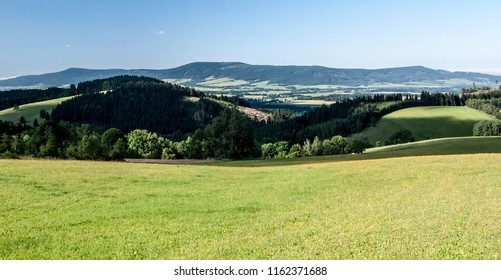 beautiful landscape of moravian - bohemian borderland near Kraliky city with meadows, countryside, Orlicke hory mountain range and clear sk from Roudny hill above Prostredni Lipka village