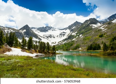 Beautiful landscape of a mountain lake Altai, Siberia. High mountains with snow-capped mountains, blue sky with beautiful clouds.