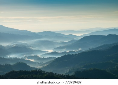 Beautiful Landscape of mountain layer in morning sun ray and winter fog at Chiangrai, Thailand