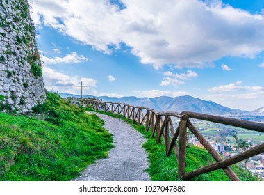 Beautiful landscape, mountain path with a wooden fence and steel cross. The Italian Apennines.
