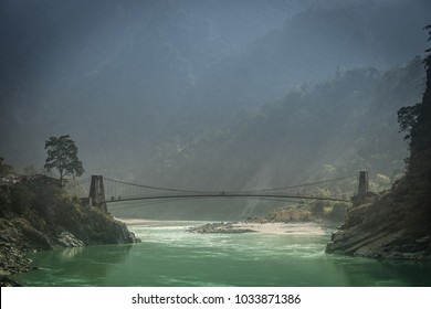 A beautiful landscape in the mountains with a bridge over the Ganges River near the city of Rishikesh India