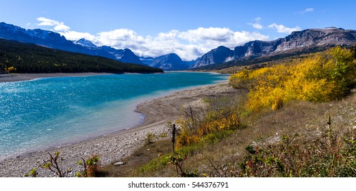 beautiful landscape in the mountains of Glacier National Park in Montana with a variety of color from different trees and vegetation surrounding the lake in late October