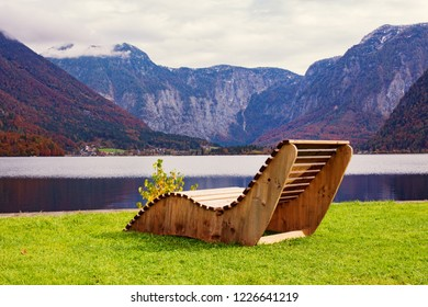 Beautiful landscape, mountains and lake, wooden deck chair in nature.