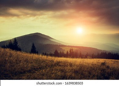 Beautiful landscape in the mountains at sunrise with haze and cloudy sky. View of the magnificent natural scenery of mountains hills.
