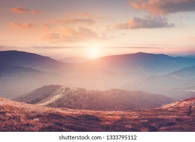 Beautiful landscape in the mountains at sunset with haze and cloudy sky. View of magnificent natural scenery of mountains hills. Filtered image:cross processed retro effect.