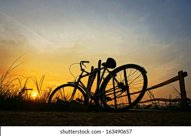 Beautiful landscape of nature with impression 's sun and silhouette of bicycle put up at wooden fence in sunrise at countryside
