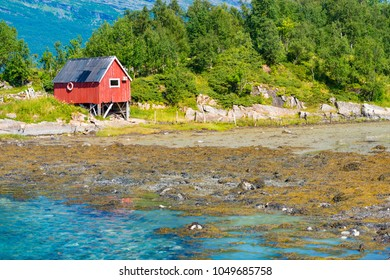 Beautiful landscape of Norway. Red barn, trees and water, mountains in background. Travel in Scandinavia, Europe.