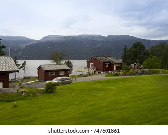 Beautiful landscape of the Norwegian fjords with water colored houses on the shore and trees on the coast