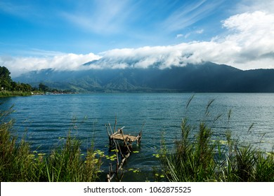 Beautiful landscape and old fishing pier on Beratan Lake in Bali Indonesia an early morning on background of high mountains with clouds