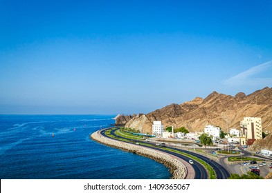 Beautiful landscape of Oman with a curvy seaside road, mountains, blue sky and blue sea. From Muttrah, Muscat.