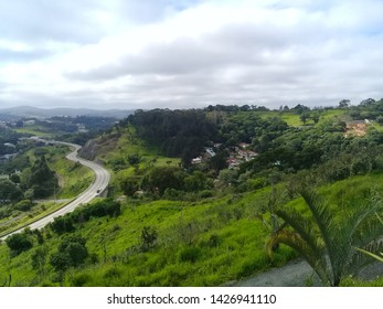 Beautiful landscape of one of the many countryside cities of the state of Sao Paulo, Brazil. The white cloudy sky contrasts with the vegetation spreading everywhere and the sinuous road.