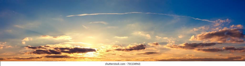 beautiful landscape panorama with blue sky, clouds and sunset. panoramic view of sunrise, a new day. sun rays shine through  clouds.