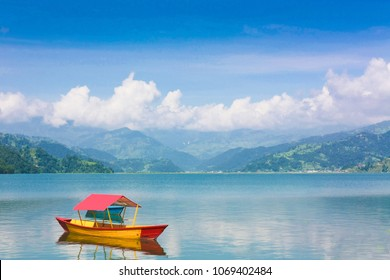 Beautiful landscape of Phewa Lake in Pokhara, Nepal. Background with colorful boat, beautiful blue sky, clouds and Himalaya mountains. Traveling Asia, Lifestyle vacations travel concept.