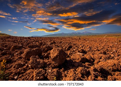 beautiful landscape with plowed field, lit by sunset light under dramatic colourful cloudy sky