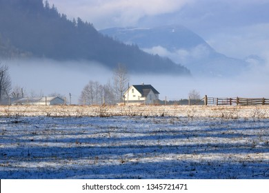 A beautiful landscape portrait of the rural winter valley and sunlight stretched across a shallow dusting of snow.