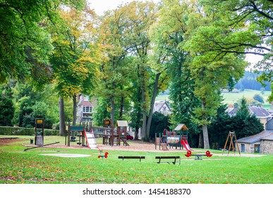 Beautiful landscape public park in village with background big green trees, field and  colorful children playground :slide, swing on modern playground.  . Activities in public park for children play