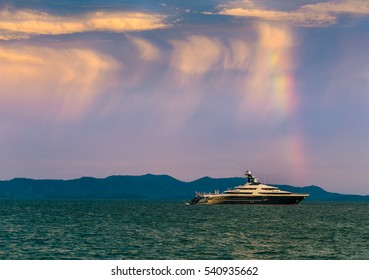 Beautiful landscape with rainbow sunset sky and super yacht on the sea