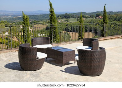 Beautiful landscape with rattan table and armchairs on country terrace, Tuscany, Italy.
