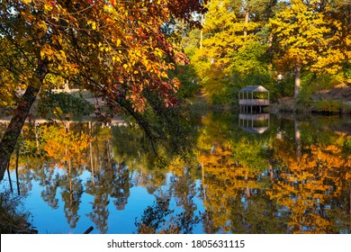 Beautiful  landscape with reflection of trees in a forest lake. Bright yellow and orange fall foliage trees reflected in water. Autumn natural background, most wonderful places in a world.