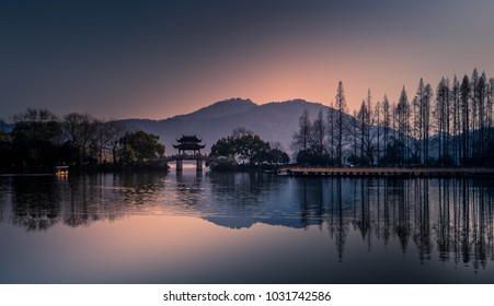 Beautiful landscape reflection views of West Lake in Hangzhou, China. Soft pink and purple reflections of trees and mountains.