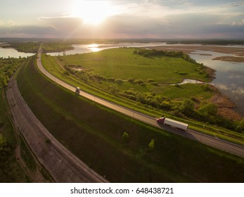 beautiful landscape with a ride on the highway the trucks and a few cars at sunset. aerial view