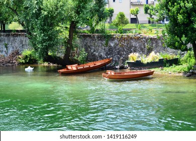 Beautiful landscape of the river Adda at the town of Lecco with wooden boats and a white swan sleeping.