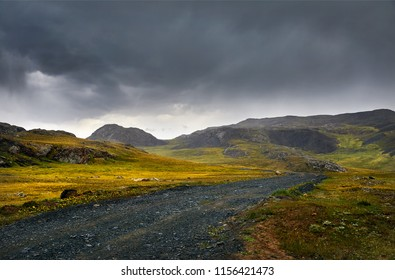 Beautiful landscape with road in the mountain valley at cloudy sky background