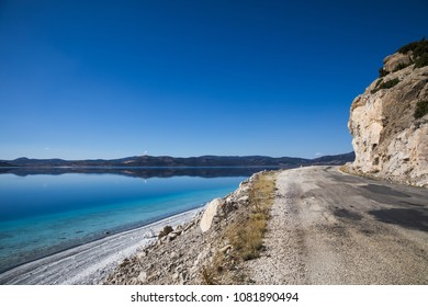 beautiful landscape with rural road, rocks and calm water, salda golu, turkey