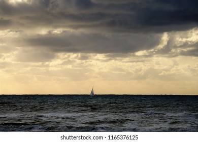 Beautiful Landscape With Sailboat And Sunset, North Sea Beach Of Scheveningen In Netherlands. Scheveningen is most popular seaside resort in Holland. Close Up. Background Of Summer Time.