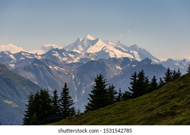 A beautiful landscape shot of Monte Rosa mountain in Switzerland with a person descending on a parachute
