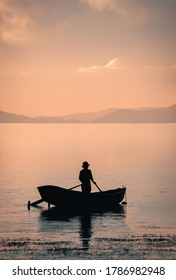 Beautiful landscape with silhouette of a man on a boat during sunset in the north side of the Isla del Sol, Bolivia