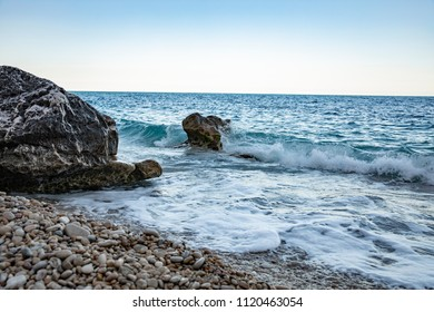 A beautiful landscape, the sky is pure blue, only a small cloud attracts the eye. The sea rumbles, rolling waves on the shore, and huge stones on the shore take blows on themselves.