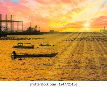The beautiful landscape of Sriracha, Chonburi(Thailand) sea port with fishery boat on golden light sunset.