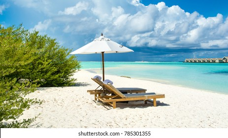 Beautiful landscape with sunbeds and umbrellas on the sandy beach, Maldives island