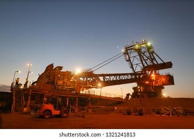 Beautiful landscape sunrise at reclaimer wheel bucket at early morning construction mine site Pilbara region Perth, Australia
