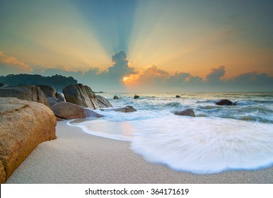 Beautiful landscape sunrise in the sea with stones on a long exposure. Soft Focus due to Long Exposure Shot
