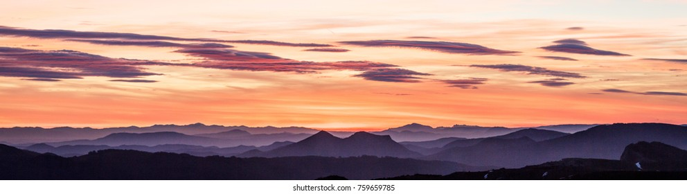Beautiful landscape at sunset with orange colors of the Pyrenees mountain range from a viewpoint at Irati green forest National Park in Navarra with the basque mountains of Aizkorri and Aralar, Spain