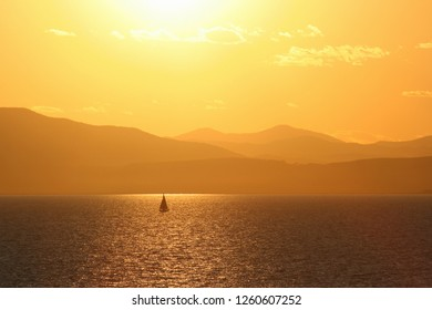 Beautiful landscape with sunset over the sea of ​​Japan. On the sea sailboat. In the distance mountains. Warm atmospheric perspective. Amur Bay, Vladivostok, Primorsky Region, Far East of Russia.