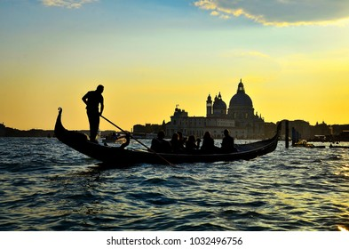 Beautiful landscape sunset view of traditional Gondolas on famous Canal Grande with historic Basilica di Santa Maria della Salute in the background in evening light at sunset in Venice, Italy