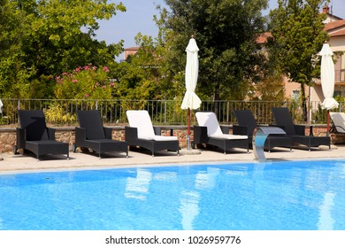 Beautiful landscape with swimming pool and deck chairs on summer resort, Tuscany, Italy