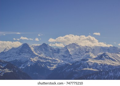Beautiful landscape of Swiss Alps mountain range in winter with peak covered by snow under blue sky white clouds, Panorama view of rock sierra and hill at Switzerland
