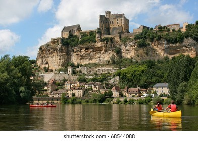Beautiful landscape with tourists kayaking on river Dordogne and Château de Beynac in the background as seen in Beynac-et-Cazenac, Southern France