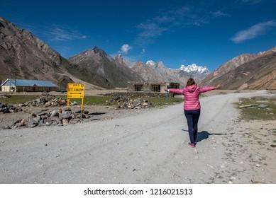 Beautiful landscape with traveller woman raised hands in Rangdum, Zanskar Range, Pensi La, Jammu and Kashmir, India.