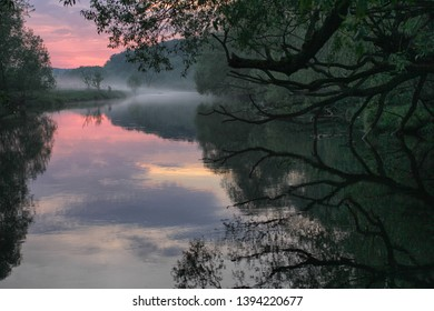Beautiful landscape with trees by the river at sunset with reflection in the water