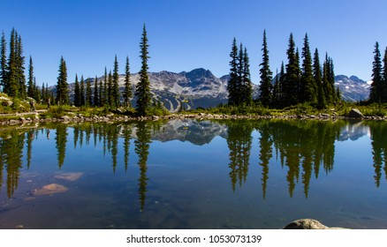A beautiful landscape view of Blackcomb Mountain viewed from Whistler with Harmony lakes reflecting the mountains as people are hiking in the distance