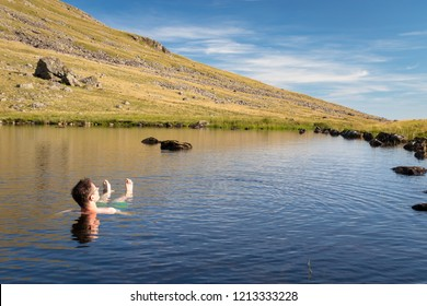 Beautiful landscape view of Greendale Tarn in the Lake District National Park, UK. A man relaxing and enjoying refreshing bath in cold tarn water on a beautiful sunny day.