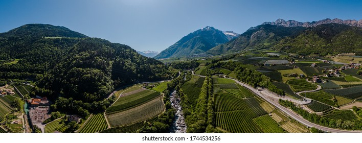 Beautiful landscape view into the val Venosta valley, Southtyrol. Apple tree fields, a river and the mountainrange in the background. Clear sky, sunny spring day. Dron shot