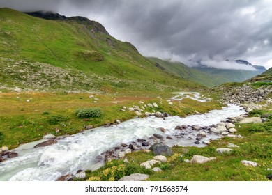 Beautiful landscape view of the Moiry glacier river of melted ice down the valley with a ominous sky with clouds in summer in the Swiss pennine alps near Grimentz, Valais, Switzerland
